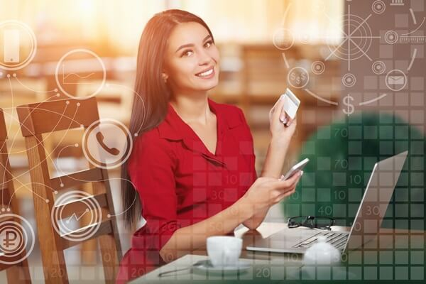 Young business woman holding mobile phone and credit card. Woman pays for a purchase with credit card and looking in camera. Purchase and shopping online. Business infographic
