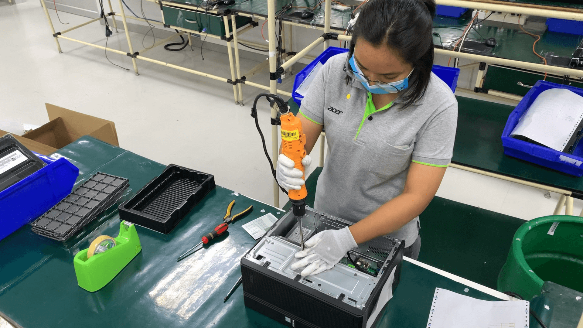 woman working in warehouse trying to fix computer