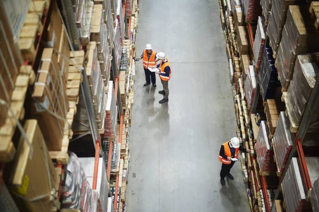 2 men are working together within warehouse