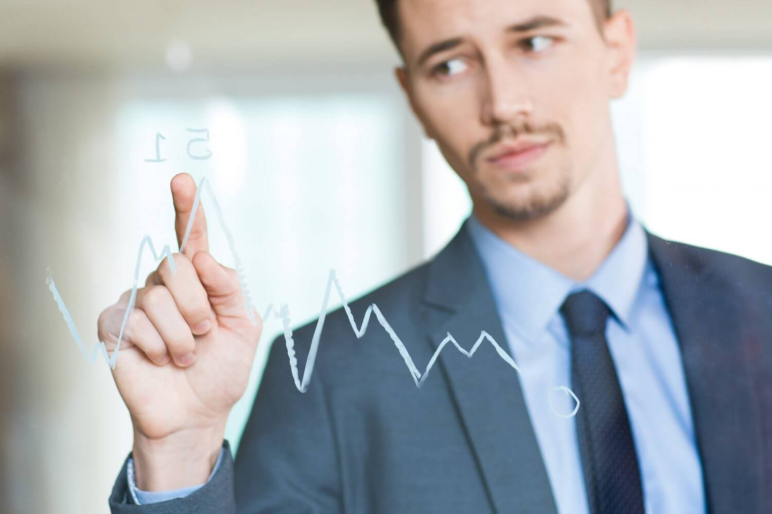 a business man is pointing at graph to analyse trends